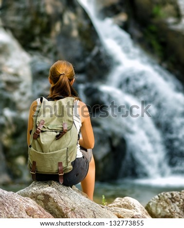 Female hiker looking at waterfall.