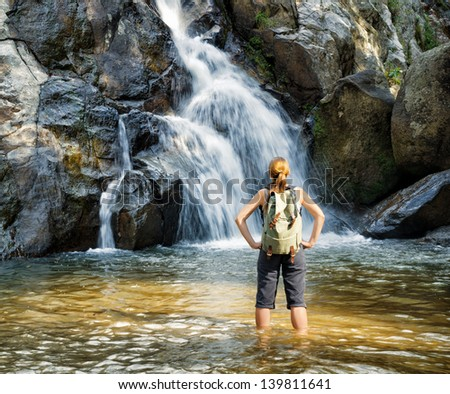 Female hiker looking at waterfall. - stock photo