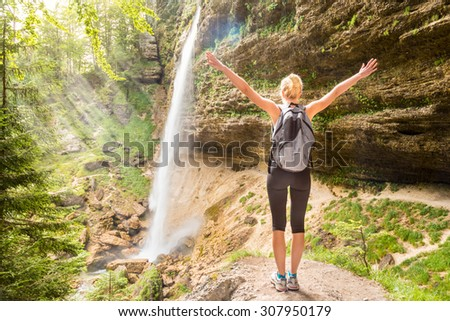 Female hiker raising arms inhaling fresh air, feeling relaxed and free in beautiful natural environment under Pericnik waterfall in Vrata Valley in Triglav National Park in Julian Alps, Slovenia. - stock photo