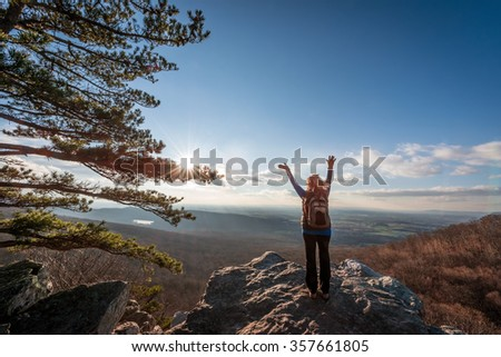 Female hiker reaching to the sky celebrating making it to the top of an Appalachian mountain and seeing the beautiful vista - stock photo