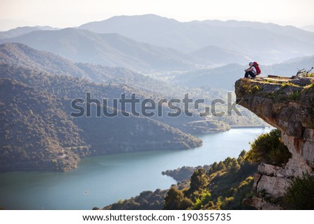 Female hiker sitting on cliff and enjoying valley view - stock photo