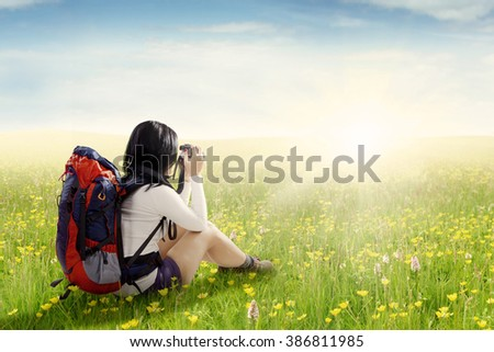 Female hiker sitting on the meadow while carrying backpack and taking pictures with digital camera - stock photo