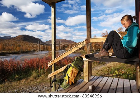 female hiker take a break on the front of a hut - stock photo