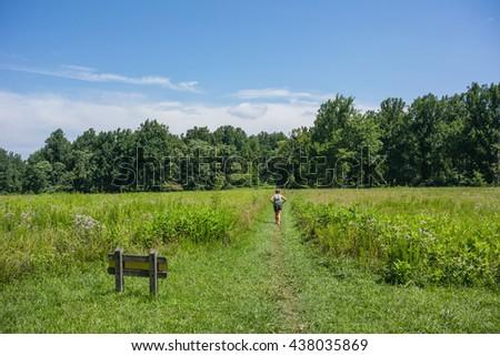Female hiker through open field in a park in Virginia along the Appalachian Trail - stock photo