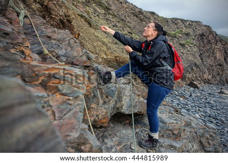 Female hiker using ropes to climb the rocks of sea cliffs in Devon, England. - stock photo