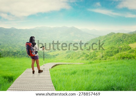 Female hiker walking on the wooden path while holding a stick and carrying backpack - stock photo