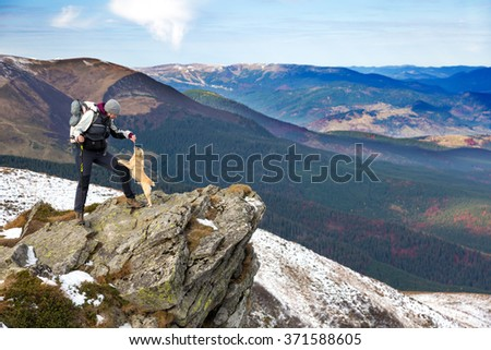 Female Hiker with Backpack and walking Poles staying at rocky Mountains Cliff and playing with accompanying Dog Scenic view with green Hills and Sky on Background - stock photo