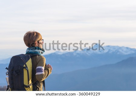 Female hiker with backpack looking at the majestic view on the italian Alps. Mist and fog in the valley below, snowcapped mountain peak in the background. Selective focus. - stock photo