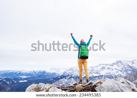 Female hiker with backpack raised her hands celebrating successful climb to top of mountain - stock photo