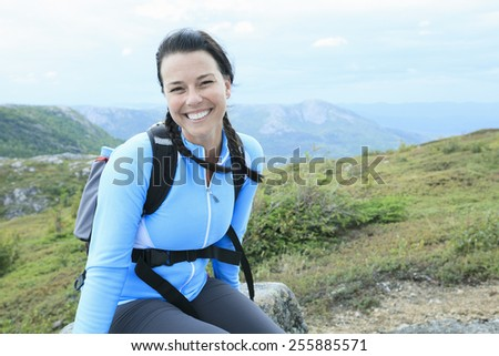 Female hiker with backpack walking and smiling on a country trail