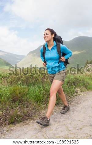 Female hiker with backpack walking on a country trail - stock photo