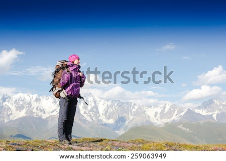Female hiker with backpack walking on the mountain trail - stock photo