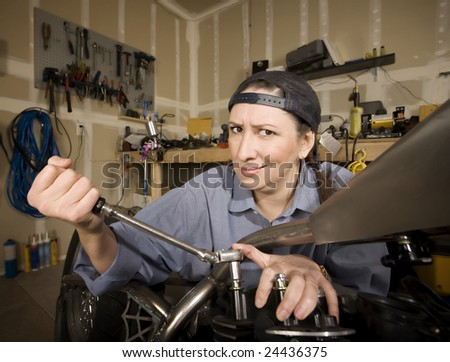 Female Hispanic mechanic working on a chopper style motorcycle - stock photo
