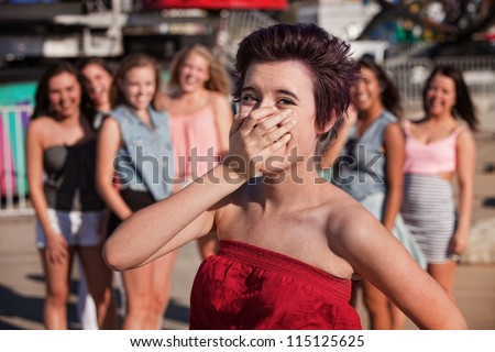Female Hispanic teenager covering her mouth while laughing - stock photo