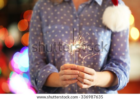 Female holding beautiful sparkler on Christmas background at home - stock photo