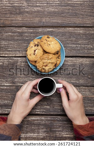 Female holding cup of coffee near cookies on wooden background  - stock photo