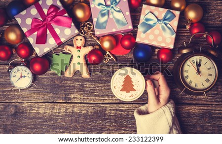 Female holding cup of coffee with cream christmas tree on a table near toys. - stock photo