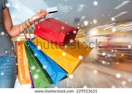 Female holding shopping bags at shopping mall. Christmas and holidays concept