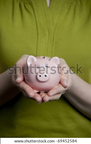 Female holds piggy bank in hands. - stock photo