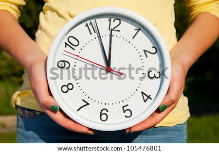 Female holds watches staying outdoors - stock photo