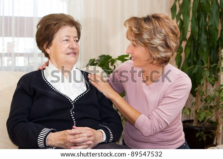 Female home giver hugging senior woman in the living room. - stock photo