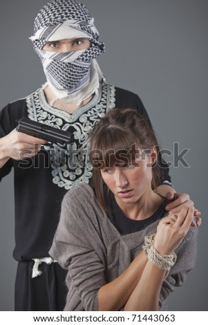 female hostage and hijacker with gun over grey background - stock photo