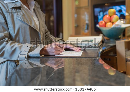 female hotel guest filling in registration form upon checking in, service and tourism concept - stock photo