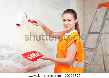 Female house painter paints wall with roller - stock photo