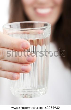 Female human hand holding liquid drink water glass - stock photo