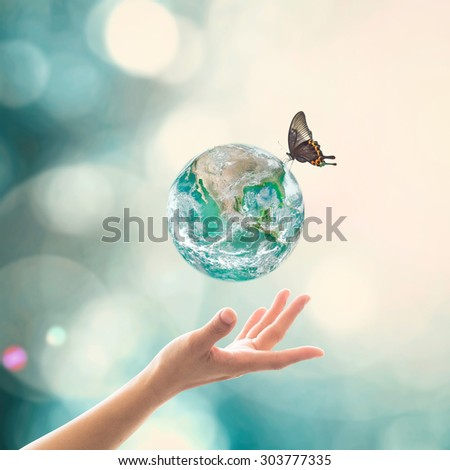 Female human hand reaching beautiful earth and butterflies with bokeh and sun flare on blurred green vintage sky tone background: Clean environment concept: Elements of this image furnished by NASA   - stock photo