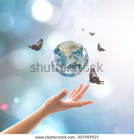 Female human hand reaching beautiful earth hour, butterfly, bokeh and sun flare on blur blue sky background: Clean environment and climate change CSR concept: Element of this image furnished by NASA - stock photo