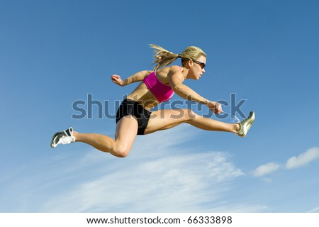 Female hurdler jumps against a blue sky in the background. - stock photo