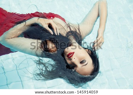 Female in a red dress swimming in the pool - stock photo