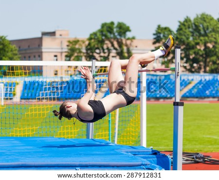 female in athletics competitions on high jump - stock photo
