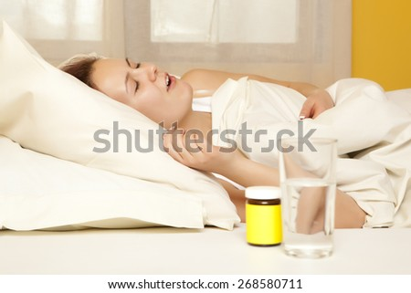 Female in bed at home caught cold, feeling bad, taking medicines, sleeping - stock photo