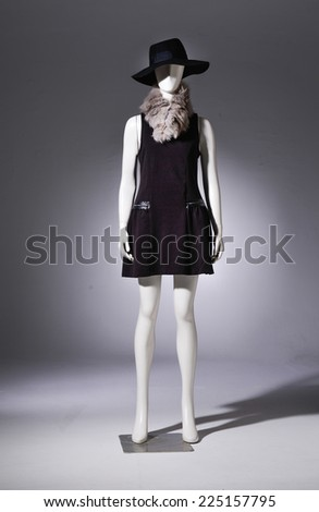 female in black shirt with hat ,scarf on mannequin - stock photo