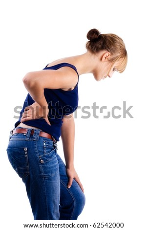 Female in blue shirt and jeans holding lower back in pain - stock photo