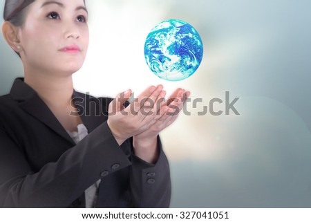 female in business uniform holding global earth floating over blurred light background in love earth concept Elements of this image furnished by NASA - stock photo
