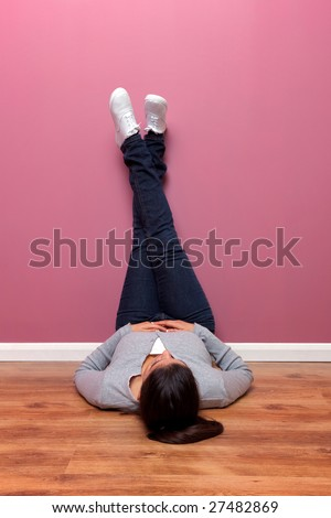 Female in casual clothing lying on the floor with her feet up against the wall - stock photo