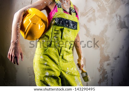 Female in coverall holding paint brush and hardhat over obsolete white background - stock photo