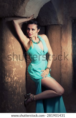 Female in gown with sexy legs posing near ancient column - stock photo