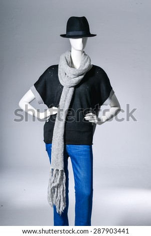 female in jeans with scarf, black hat on mannequin on light background - stock photo