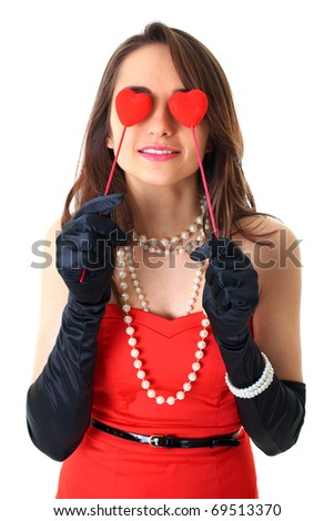 female in red dress holds two small red hearts in front of her eyes, love is blind concept, isolated on white - stock photo