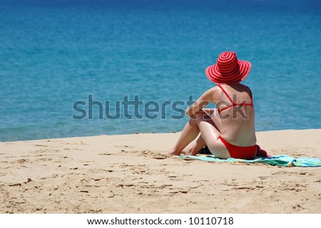 female in red sailor-hat on a background of the tropical beach - stock photo