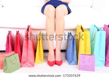 Female in red shoes sitting on sofa with shopping bags close up - stock photo