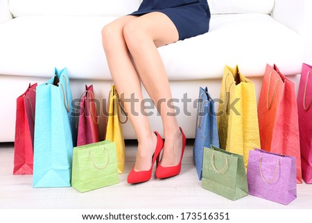 Female in red shoes sitting on sofa with shopping bags close up