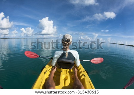 Female in sea Kayak from Behind. - stock photo