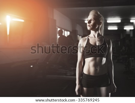 Female in sports clothing relaxing after workout on the gym grey background. Muscular female body with sweat. Copy space for text. Posters and advertising for gym. Woman in sports wear standing. Sort