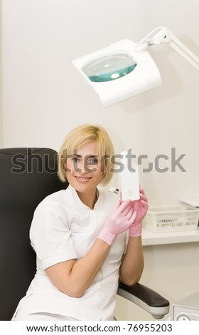 Female in the white uniform holds bottle and smiles - stock photo
