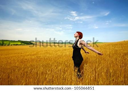 Female in wheat field enjoying summer - stock photo